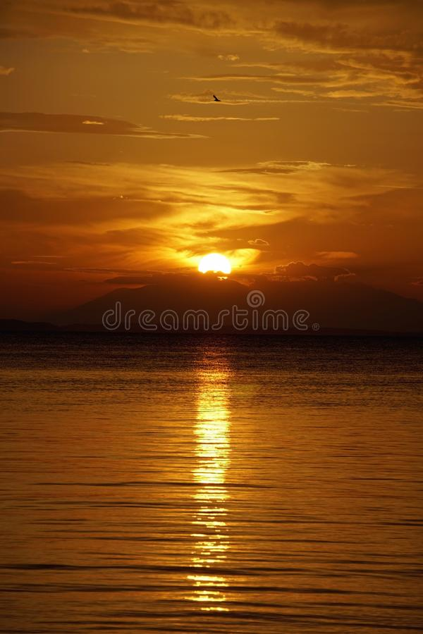 Il tramonto rosso scarlatto sul mare Settembre in Grecia Sithonia Il sole e le nuvole e i colori insoliti Glare sull'acqua fotografia stock libera da diritti