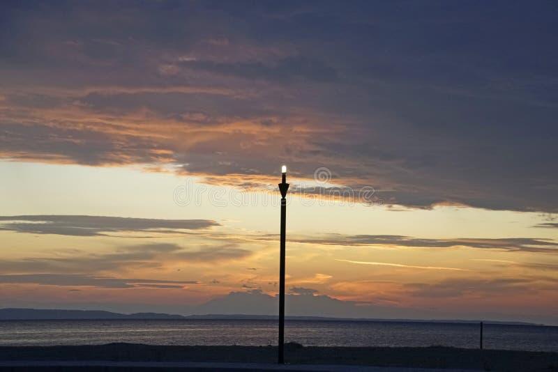 Il tramonto rosso scarlatto sul mare Settembre in Grecia Sithonia Il sole e le nuvole e i colori insoliti Glare sull'acqua immagini stock