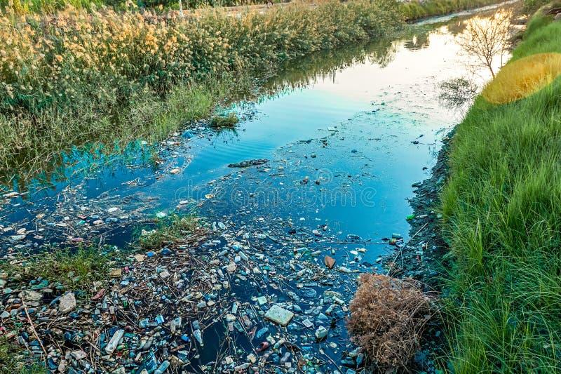 Il tramonto sopra il canale è inquinato da rifiuti e da plastica fotografie stock