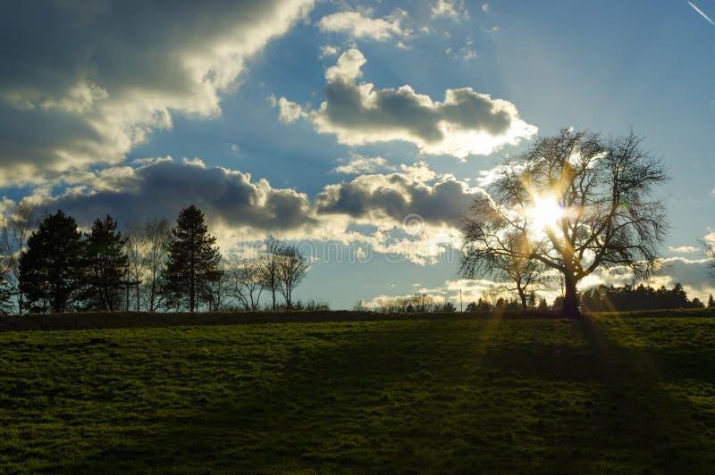 Il tramonto stupefacente sopra un paesaggio verde scuro della campagna di Rolling Hills con il sole irradia il cielo penetrante e immagine stock
