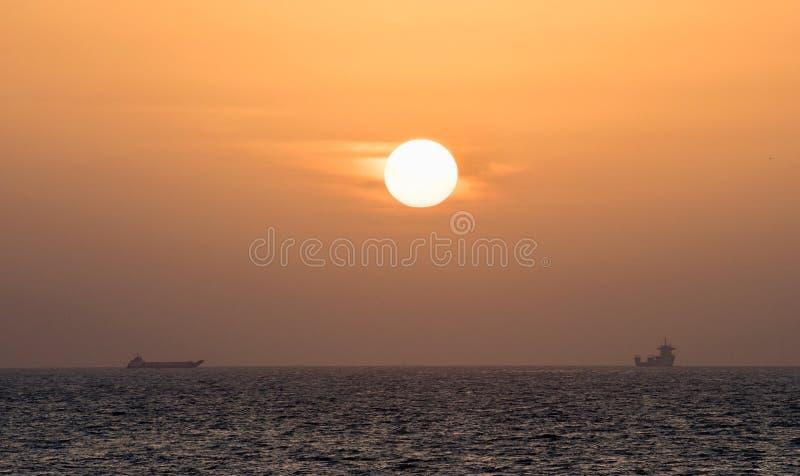 Il tramonto variopinto nel mare, le navi va incontrarsi immagini stock