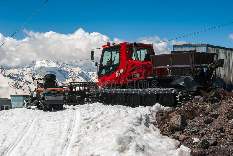 Il trasporto rosso di gatto delle nevi su neve bianca pulisce la pista dello sci vicino al riparo della montagna Montagna di Cauc immagini stock