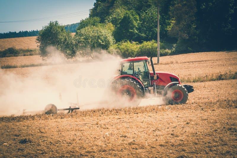 Il trattore ara un campo - concetto di agronomia e dell'agricoltura immagini stock libere da diritti