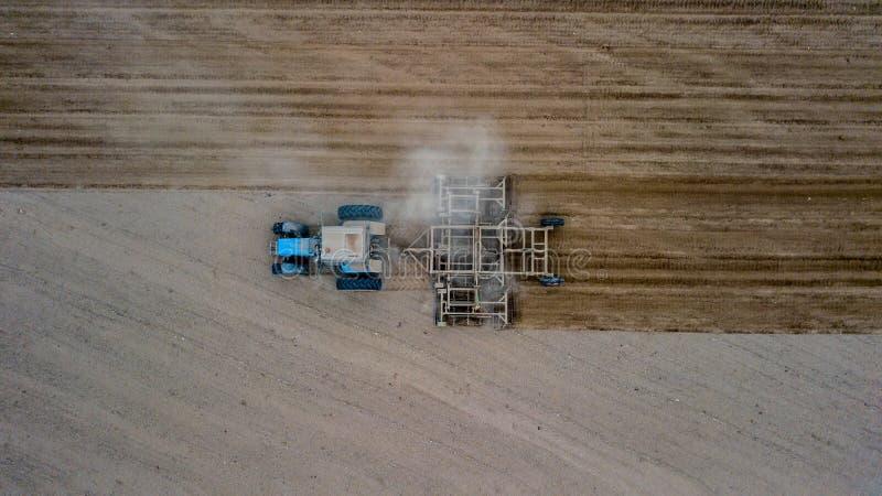 Il trattore che coltiva il campo alla molla, la lavorazione è la preparazione agricola di suolo da agitazione meccanica di vario  fotografia stock libera da diritti