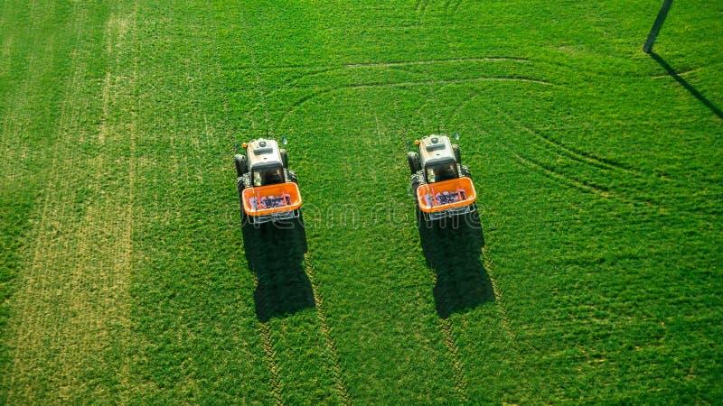 Il trattore fa il fertilizzante sul campo Rilevamento aereo fotografia stock libera da diritti