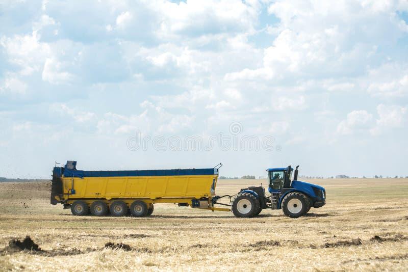 Il trattore fertilizza il campo con concime Un grande rimorchio sowing Agroindustria Palo prima della semina immagini stock libere da diritti