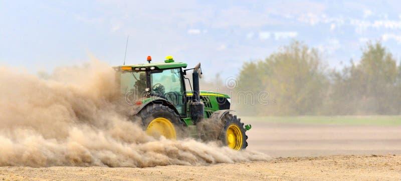 Il trattore harrows il campo in una nuvola di polvere enorme immagine stock libera da diritti