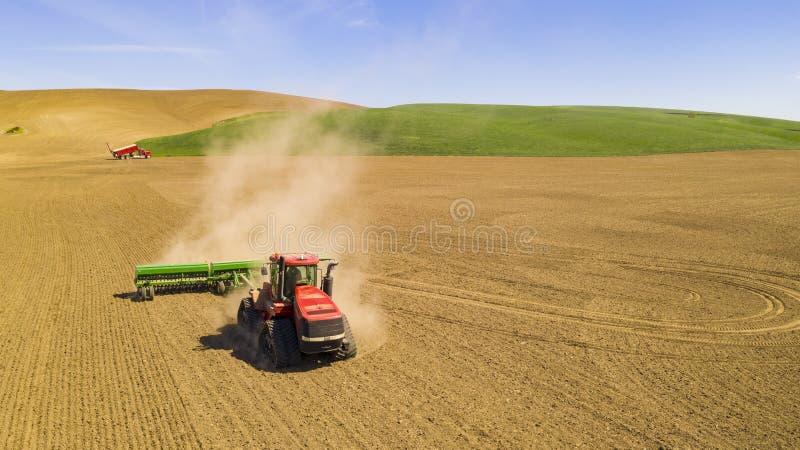 Il trattore rosso rimorchia l'aratro nel campo agricolo dell'azienda agricola immagini stock libere da diritti