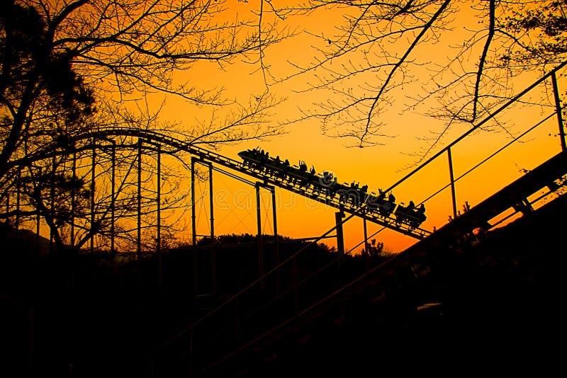 Il treno delle montagne russe sta andando in su al tramonto di autunno immagine stock libera da diritti