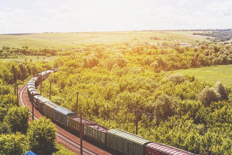 Il treno merci guida attraverso il paesaggio naturale dell'estate, binario ferroviario, concetto del trasporto del treno fotografia stock libera da diritti
