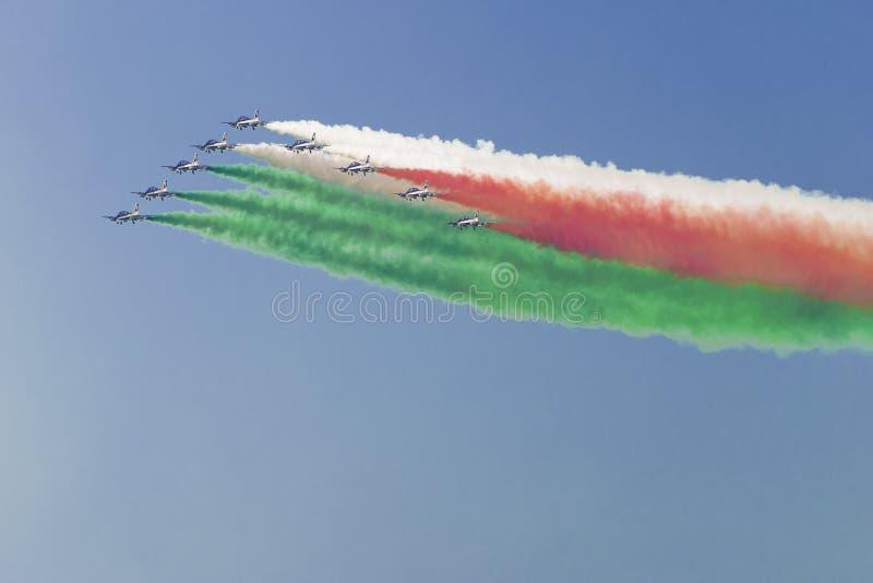 Il tricolore acrobatico di Frecce degli aerei fa la bandiera italiana in SK fotografia stock libera da diritti