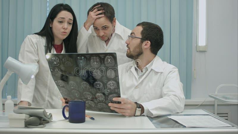 Il trio di giovani medici impauriti che controllano il ` paziente s dirige l'esame immagine stock