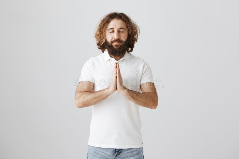 Il trouve la paix dedans pour prier Tir d'intérieur de mâle oriental décontracté et heureux avec la barbe étreignant des paumes a photographie stock libre de droits