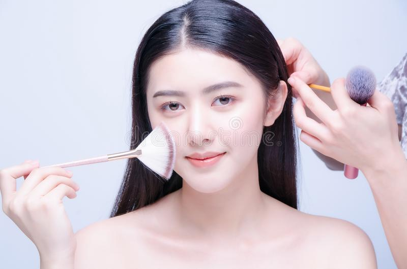 Il truccatore applica i capelli e lo skintone Bello fronte asiatico della donna Trucco perfetto Fondamento di Skincare fotografia stock libera da diritti