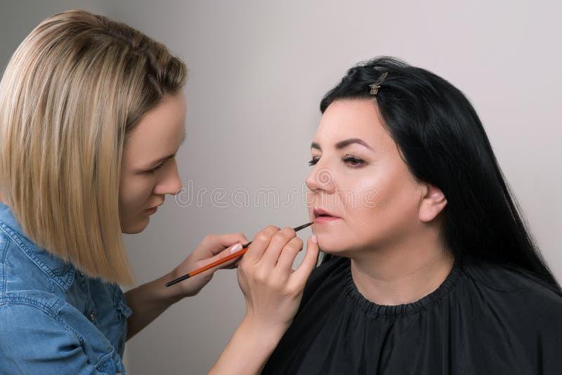 Il truccatore applica il rossetto Bella donna matura al salone di bellezza Truccatore che fa trucco per la donna affascinante Sen fotografia stock libera da diritti