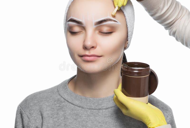 Il truccatore coglie le sue sopracciglia, prima della procedura di trucco permanente immagine stock