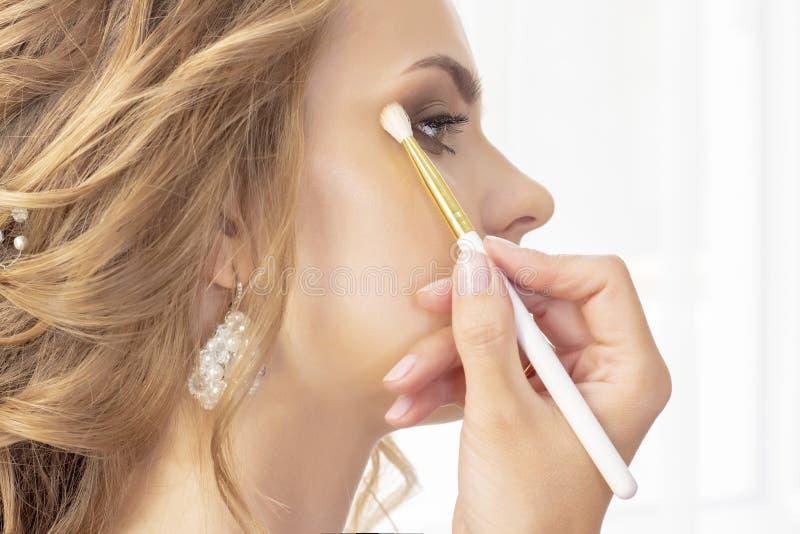 Il truccatore mette il trucco sul modello della ragazza La spazzola applica le ombre, correttore bello modello della ragazza, rit fotografia stock libera da diritti