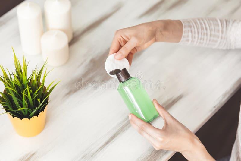 Il trucco rimuove la cura di pelle Tampone di cotone della tenuta della donna del primo piano e cosmetico liquido del dispositivo fotografia stock