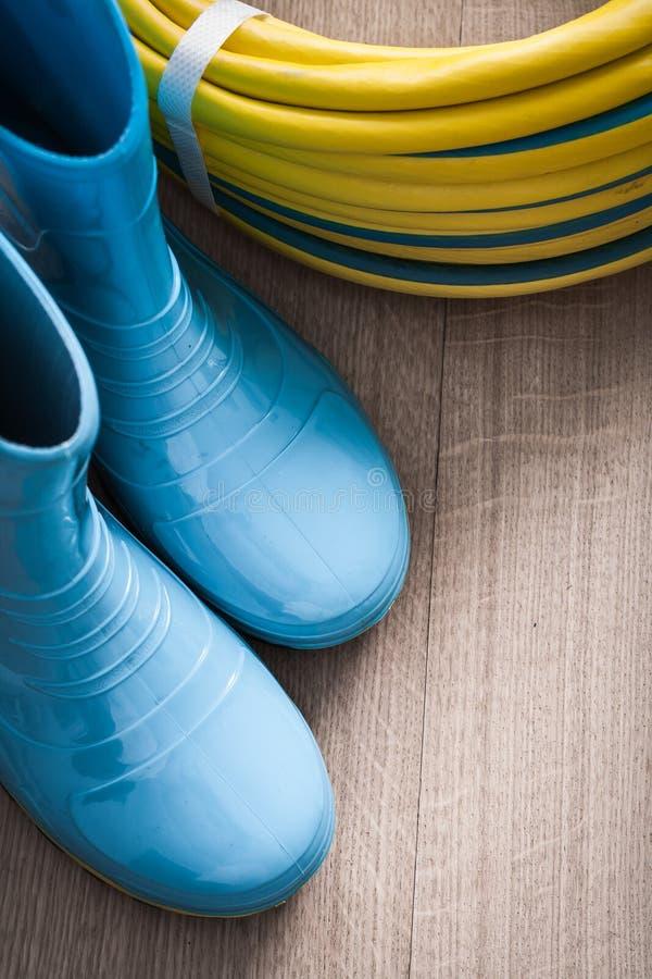 Il tubo flessibile di giardino torto ed impermeabilizza gli stivali di gomma sopra fotografie stock
