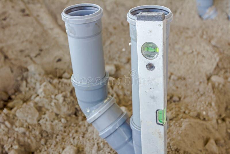 Il tubo per fognatura di plastica sta livellando con lo strumento livellato su un constructio immagine stock libera da diritti