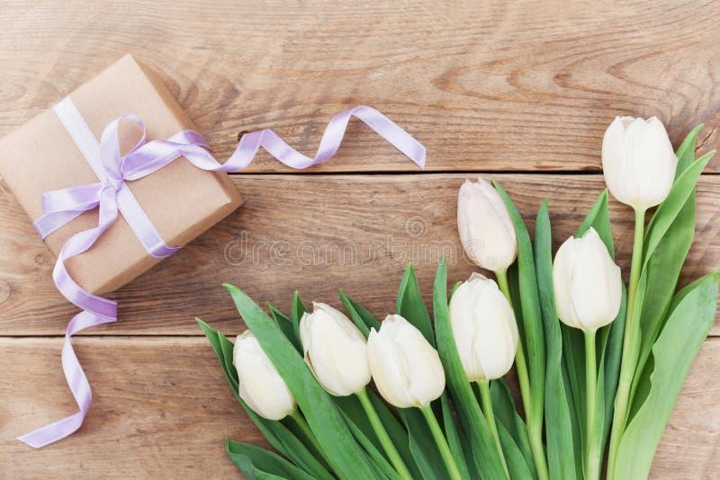 Il tulipano della primavera fiorisce ed il contenitore di regalo sulla vista d'annata del piano d'appoggio in piano pone lo stile immagine stock libera da diritti