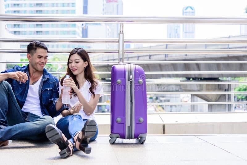 Il turista asiatico delle coppie ha acqua che beve e con la grande borsa porpora fotografia stock