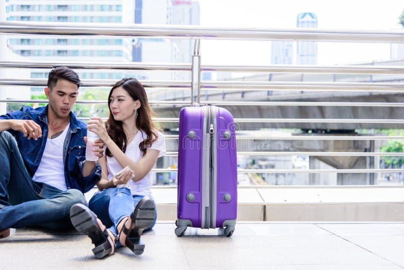 Il turista asiatico delle coppie ha acqua che beve e con la grande borsa porpora fotografie stock