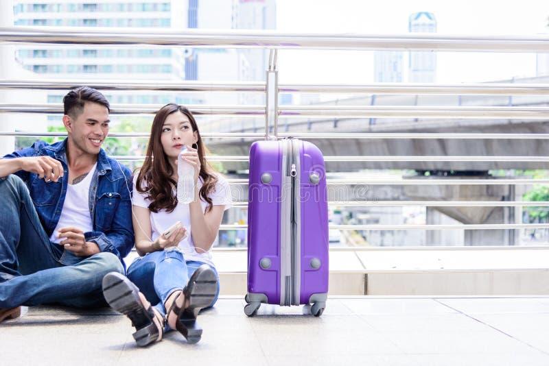 Il turista asiatico delle coppie ha acqua che beve e con la grande borsa porpora fotografia stock libera da diritti