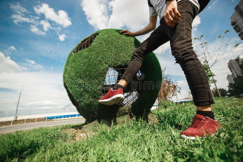 Il turista bello alla moda dell'uomo sta dando dei calci al pallone da calcio della palla di erba Concetto russo della coppa del  fotografie stock
