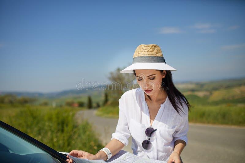 Il turista con una mappa all'automobile controlla l'itinerario al destinat fotografia stock