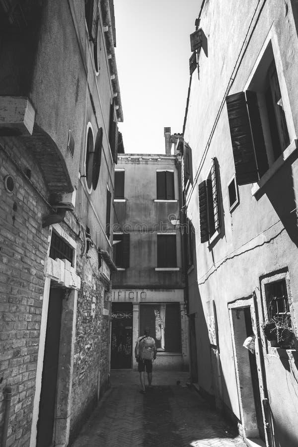 Il turista con uno zaino arancio e la bandana cammina lungo la via stretta in Europa L'Italia Venezia di estate La facciata di ve immagini stock