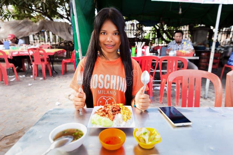 Il turista del viaggiatore della giovane donna gode di una prima colazione deliziosa immagine stock