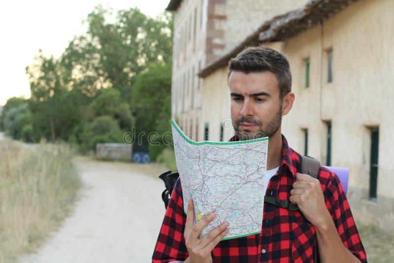 Il turista dell'uomo in campagna europea ha letto la mappa Concetto di turismo Uomo con la mappa nelle mani del viaggiatore immagine stock libera da diritti