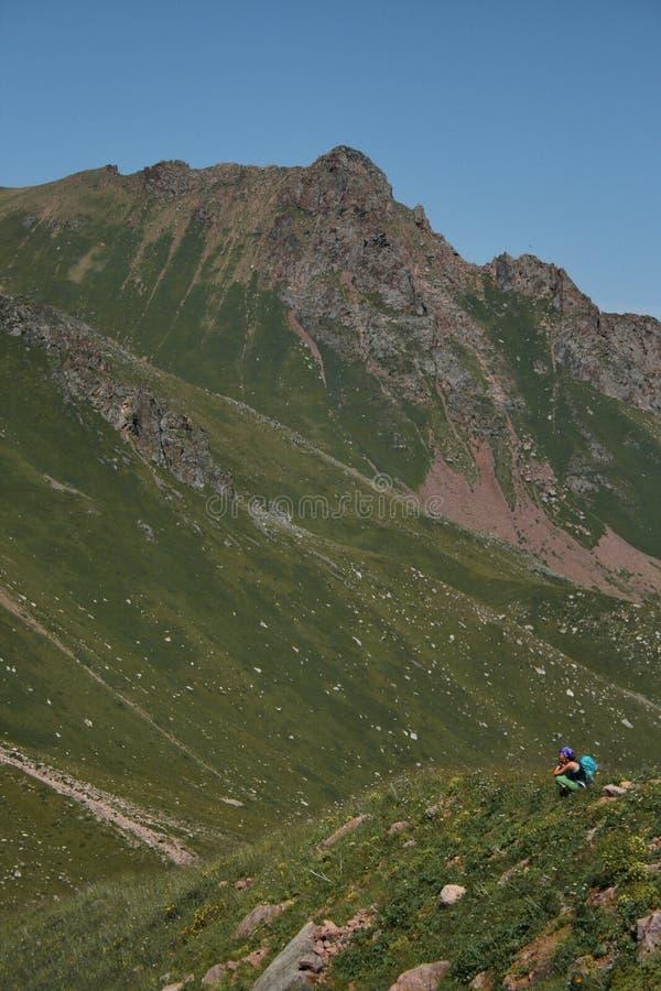 Il turista della donna con lo zaino si siede sull'orlo del canyon fotografie stock