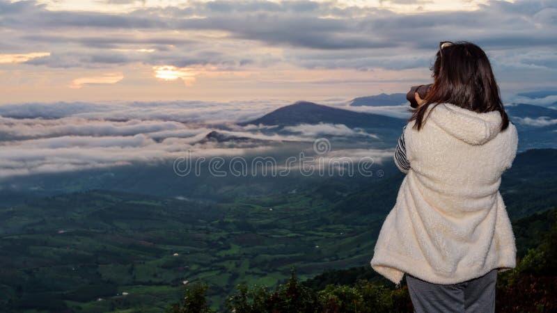 Il turista della donna sta utilizzando una macchina fotografica di DSLR che fotografa il paesaggio della natura la montagna della immagine stock libera da diritti