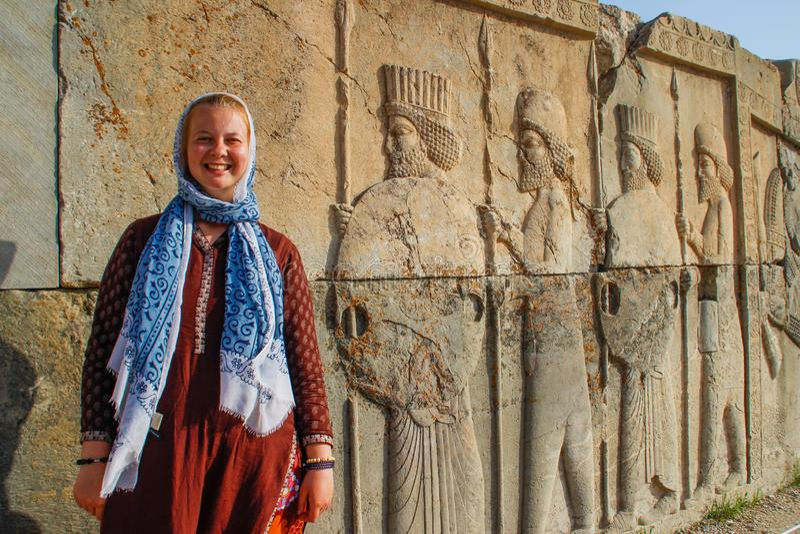 Il turista della giovane donna con una testa coperta sta sui precedenti dei bassorilievi famosi della capitale di Persia Iran - P fotografia stock libera da diritti