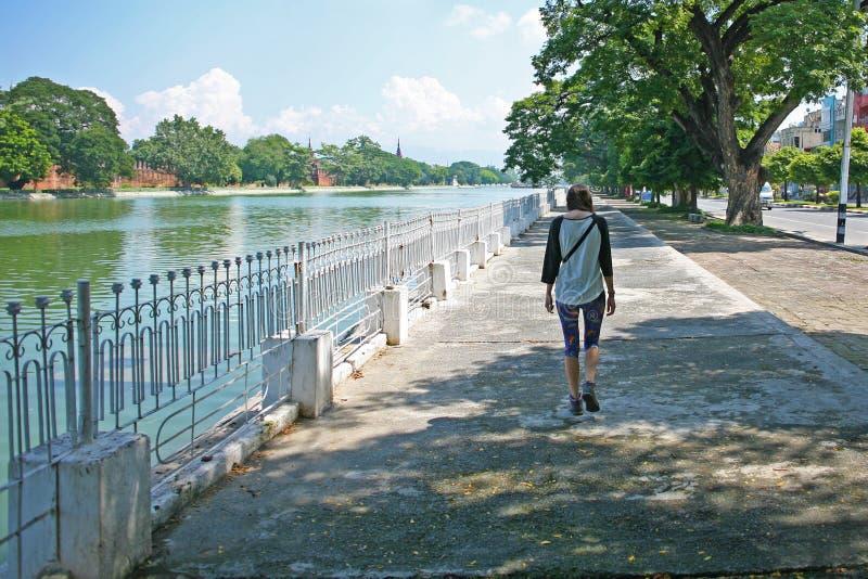 Il turista della giovane signora cammina accanto al fossato del complesso del palazzo di Mandalay un giorno soleggiato in Birmani immagine stock libera da diritti