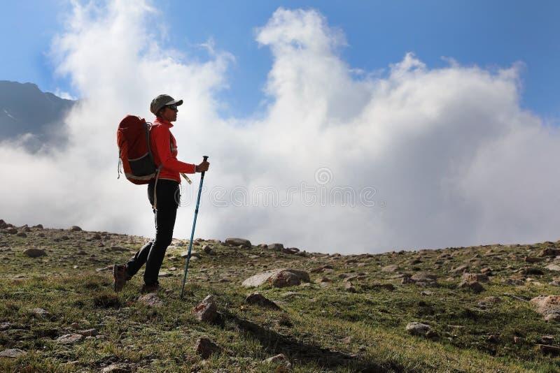 Il turista della ragazza sta sopra una montagna fotografie stock