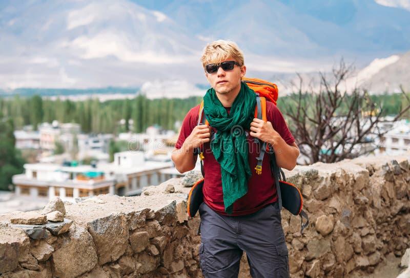 Il turista di viaggiatore con zaino e sacco a pelo arriva in settelment del tibetano della montagna fotografie stock libere da diritti