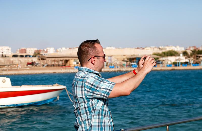 Il turista ed il viaggiatore sul pilastro della spiaggia sta prendendo ad immagini facendo uso della macchina fotografica il suo  immagini stock