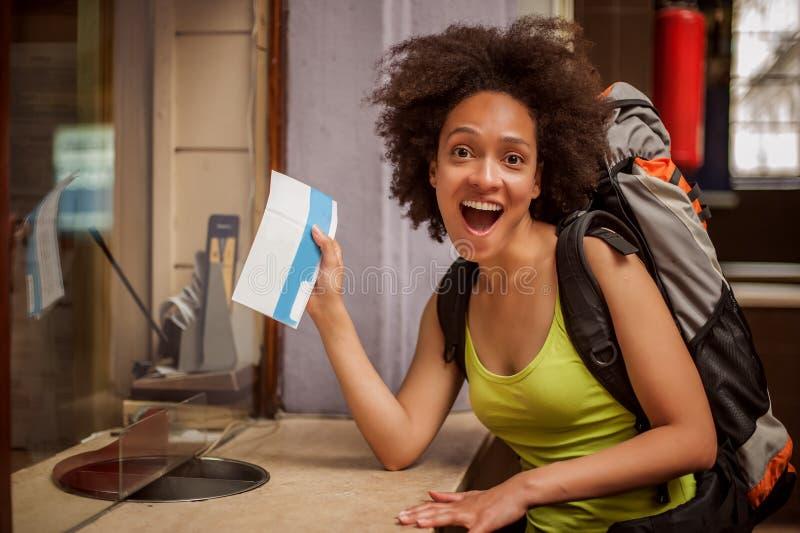 Il turista femminile di viaggiatore con zaino e sacco a pelo felice ed euforico mostra il biglietto per He immagini stock libere da diritti