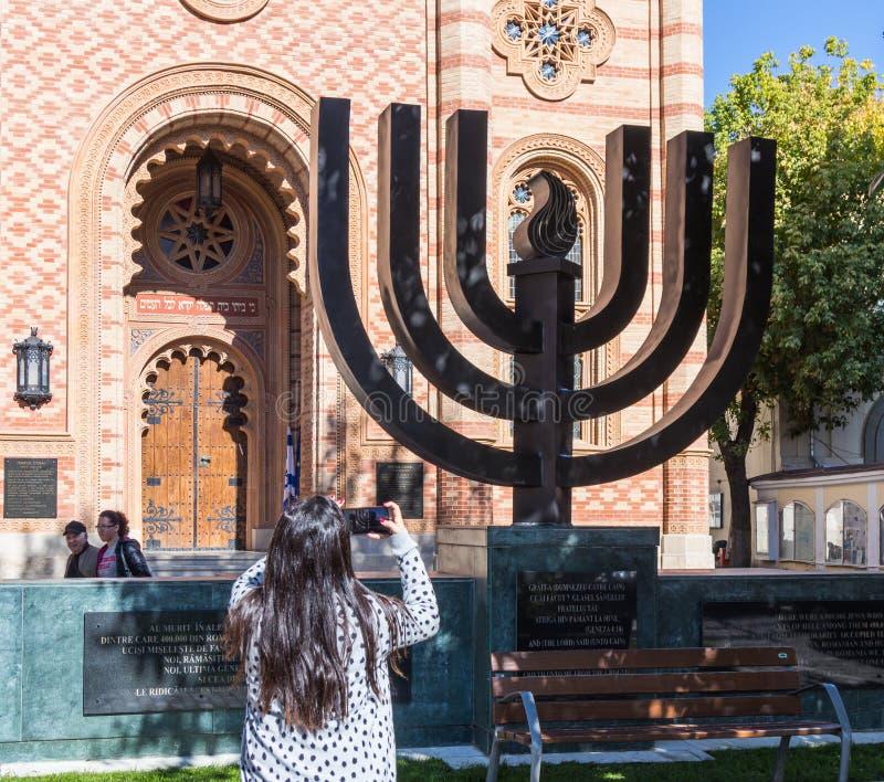 Il turista fotografa un Menorah che sta all'entrata al corallo della sinagoga nella città di Bucarest in Romania immagini stock