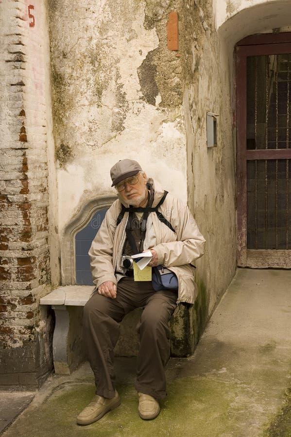 Il turista maggiore si siede su un banco fotografia stock libera da diritti