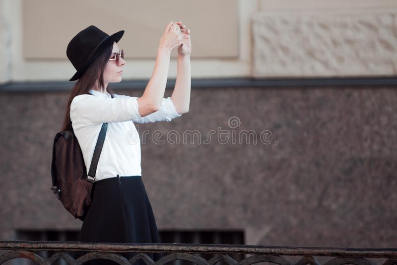 Il turista nella città prende una foto sullo smartphone Una giovane donna in una camicia black hat e bianca, fotografia stock