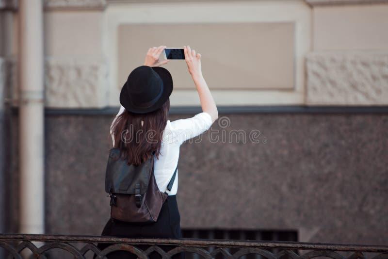 Il turista nella città prende una foto sullo smartphone Una giovane donna in una camicia black hat e bianca, immagine stock