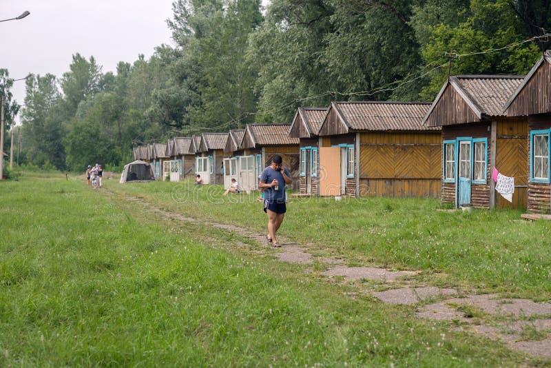 Il turista sta camminando lungo la via con le casette turistiche dell'estate di legno al campeggio di Iskra nel villaggio di Shus immagini stock libere da diritti
