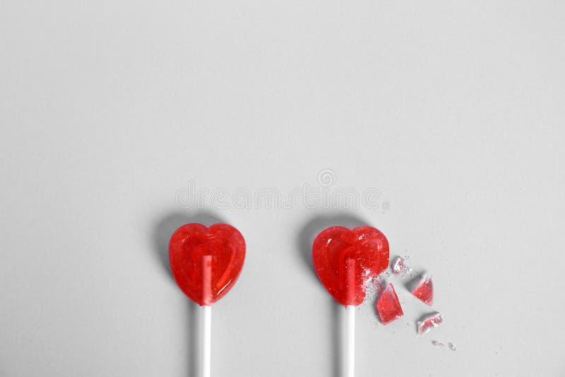 Il tutto ed il cuore rotto hanno modellato le lecca-lecca su fondo bianco, vista superiore immagine stock libera da diritti