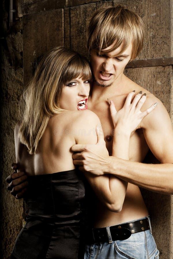 Il vampiro femminile vuole mordere un giovane fotografia stock libera da diritti
