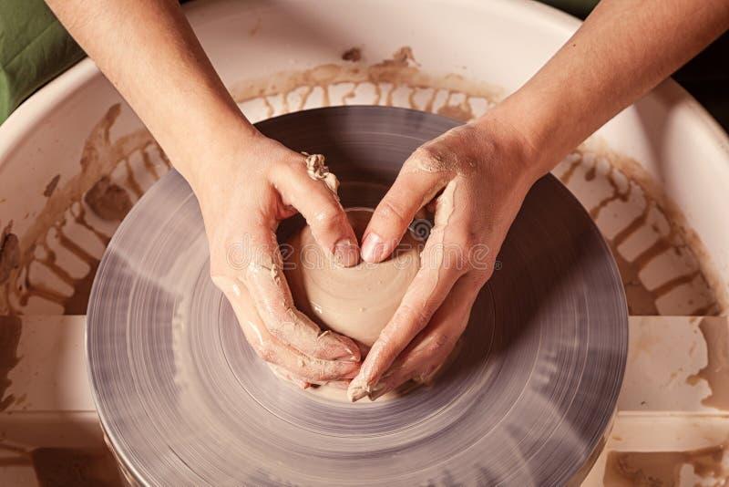 Il vasaio della donna scolpisce un'argilla fotografia stock