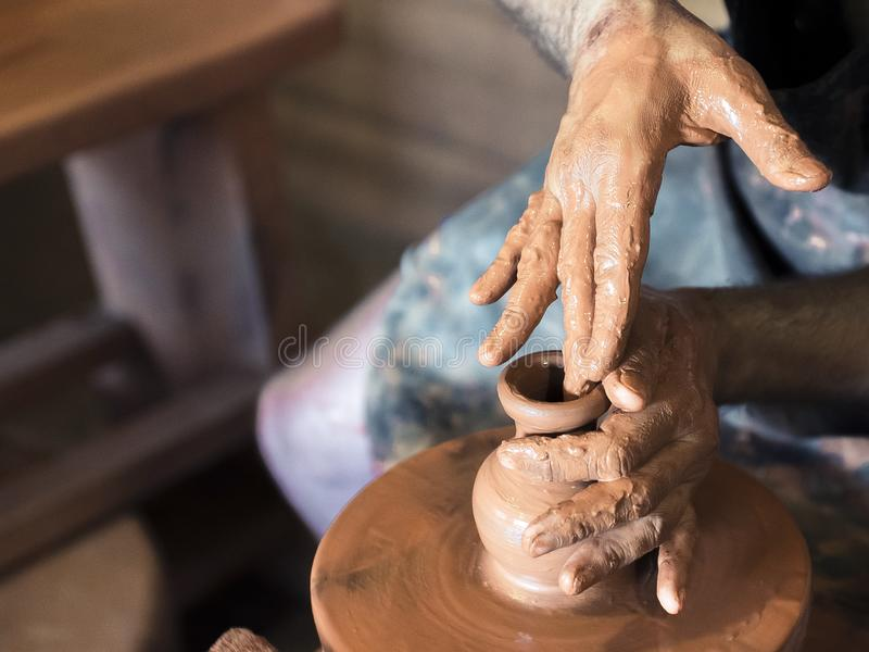 Il vasaio maschio professionista che fa la ceramica sul ` s del vasaio spinge dentro l'officina, studio Chiuda sul colpo delle ma fotografia stock libera da diritti